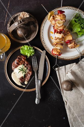 Grilled steak and chicken skewers on a plate (view from above)