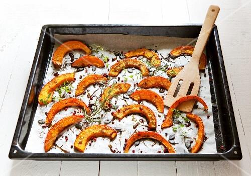 Roasted squash wedges on a baking tray