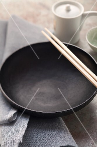 An empty black eating bowl with Asian chopsticks