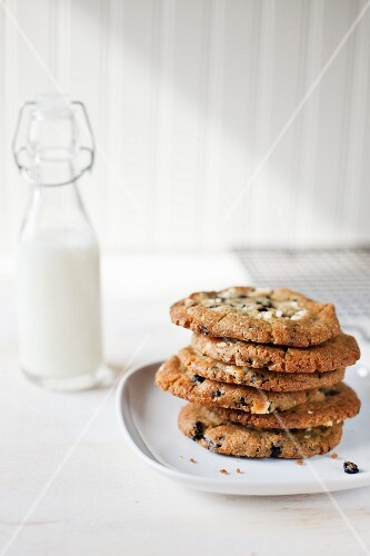 A Stack of Blueberry Cookies on a White Plate; Bottle of Milk
