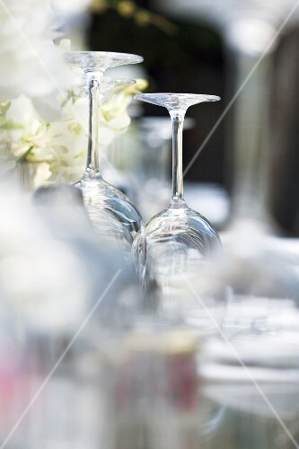 Upturned wine glasses on a table laid for a meal