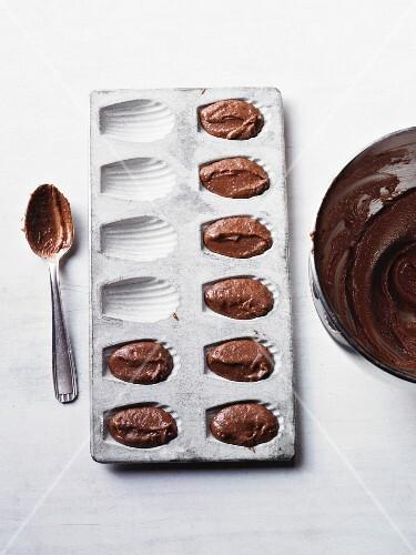 A madeleine tin with chocolate cake mixture