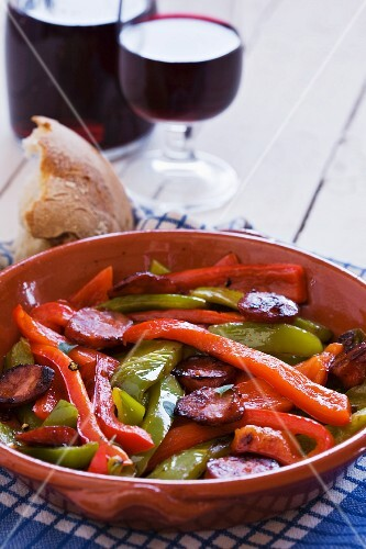 Peppers with chorizo, served with bread and red wine (Spain)
