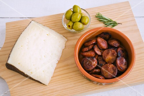 Manchego, fried chorizo slices and olives on a wooden board