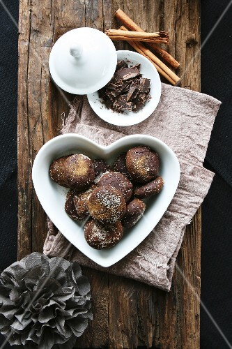 Chocolate and cinnamon treats in a heart-shaped bowl, grated chocolate, cinnamon sticks
