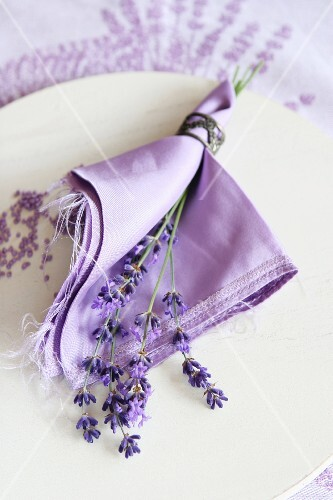Table decoration: lavender flowers and a napkin on a plate