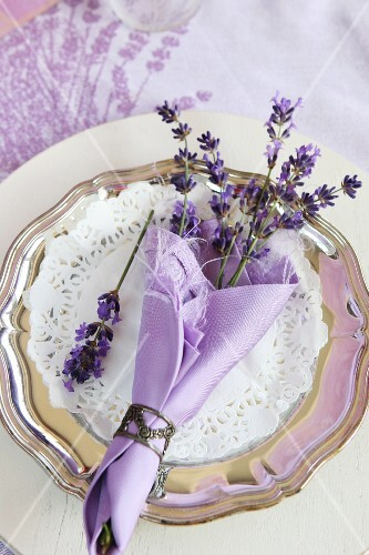 A table decoration for a celebration: lavender flowers in a purple napkin