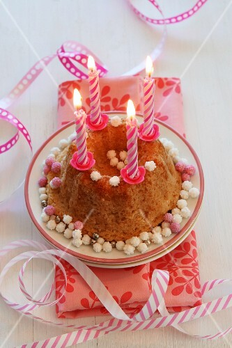 A small birthday cake with lit candles and streamers