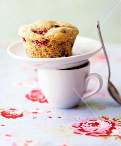 A plate with a cherry muffin on top of an espresso cup