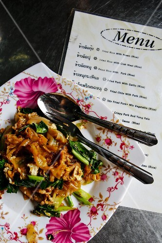 Pad Si Ew (fried rice noodles, Thailand) with a menu in a restaurant
