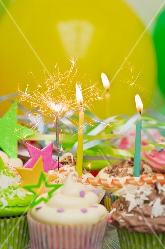 Party cupcakes with lit candles, streamers and balloons