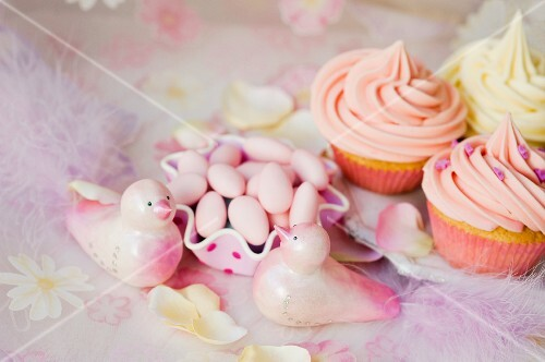 Cupcakes with buttercream, sugared almonds and pink decorative birds for a wedding