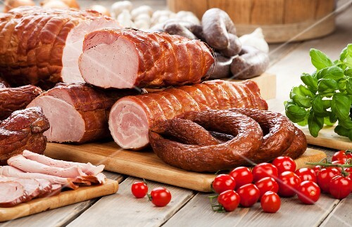 Assorted sausages and ham, cherry tomatoes, basil and garlic