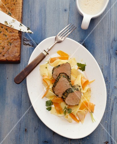 Veal fillet with a herb crust on ribbon pasta and carrot strips