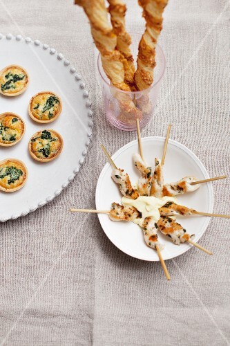 Assorted party snacks (mini spinach quiches, cheese straws, satay skewers)