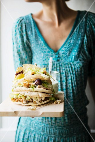 A woman serving pita bread with chicken salad, grapes, and a garlic, tarragon & cheese dressing