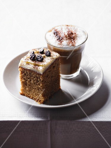 A cube of cappuccino cake and a glass of cappuccino