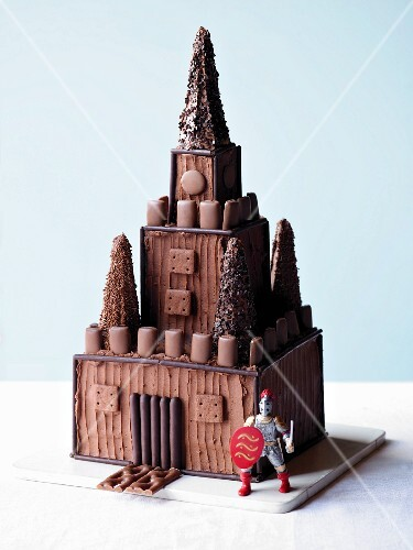 A cake designed to look like a knight's castle, with a knight figurine