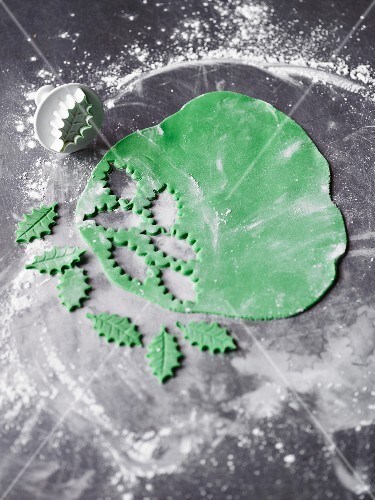 Holly leaves cut out of icing as decoration for Christmas baking