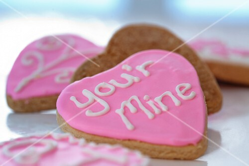 Small gingerbread hearts decorated with pink glacé icing