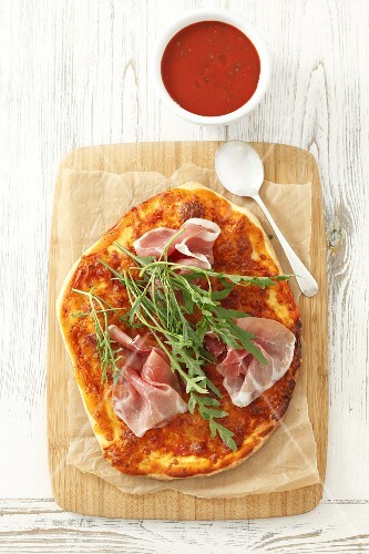 Pizza with dry-cured ham and rocket (view from above)