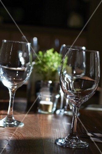 Several empty wine glasses on a wooden table in a restaurant