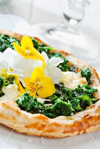 A spinach tart with edible flowers