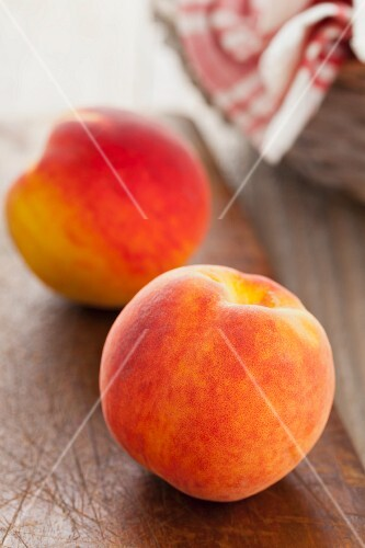 Two whole peaches on a wooden board
