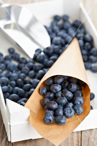 Blueberries in paper cones on a wooden crate