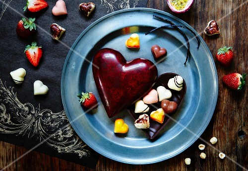 Heart-shaped chocolates with a heart-shaped chocolate box and strawberries