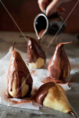 Liquid chocolate being poured over poached cinnamon pears