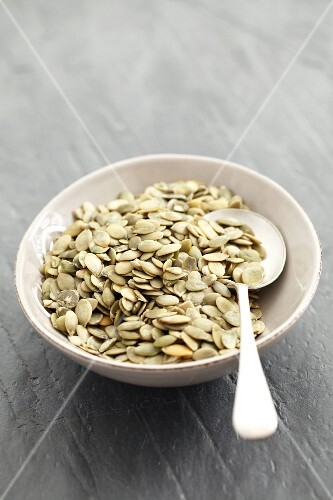 Pumpkin seeds in a bowl with a spoon