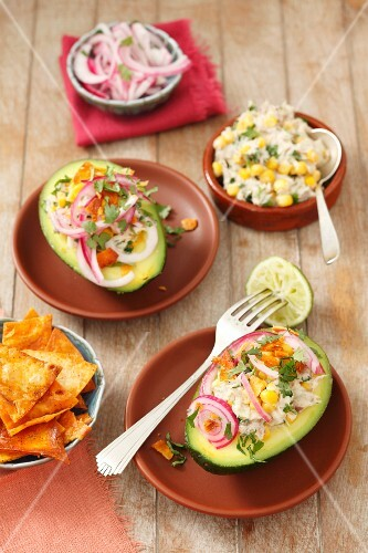 Avocado filled with smoked mackerel and a sweetcorn salad, topped with red onions and served with tortilla chips