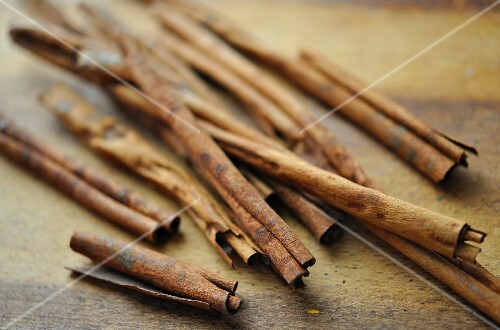 Several cinnamon sticks on a wooden board
