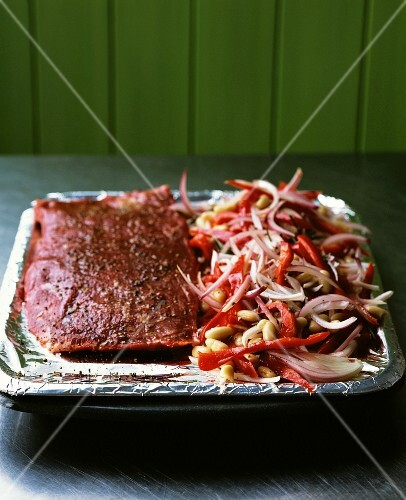 A joint of beef and vegetables in a roasting tin with aluminium foil