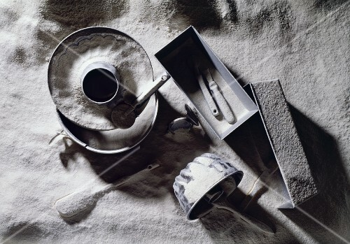 Baking tins and utensils in flour (black and white image)