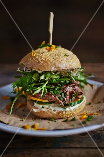 A burger bun filled with beef and rocket