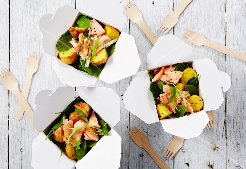 Salmon with spinach and saffron potatoes in takeaway containers