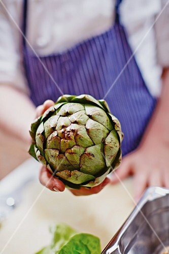 A hand holding a fresh artichoke