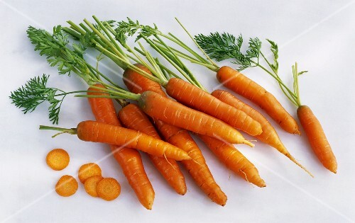Several whole carrots and slices of carrot