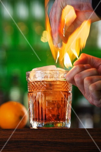 A flaming cocktail with orange