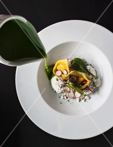 Spinach soup with ravioli and cream fraiche