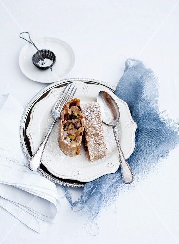 Two pieces of apple strudel with icing sugar on a plate