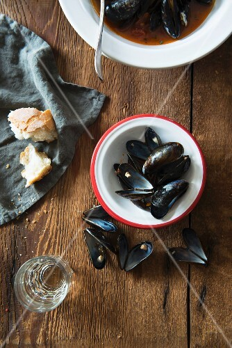 Mussel soup with tomatoes, empty mussel shells and white bread