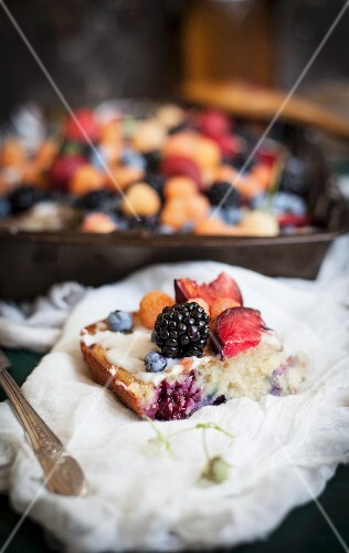 A Piece of Lavender Plum Berry Sheet Cake Topped with Mixed Berries and a Lemon Vanilla Glaze