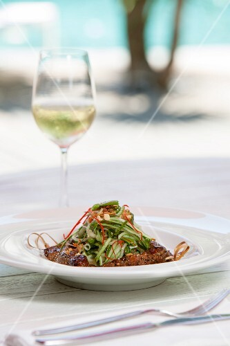 A skewer of beef satay with a cucumber salad on a table outdoors
