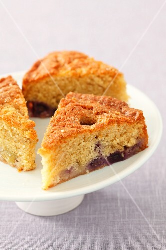 Three slices of grape cake on a cake stand
