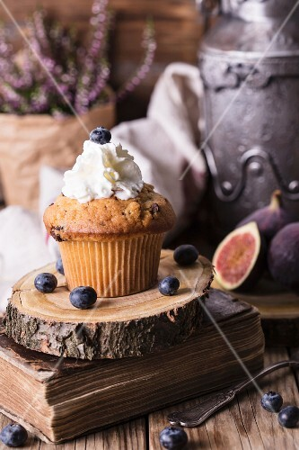 Blueberry cupcake with cream against a rustic background