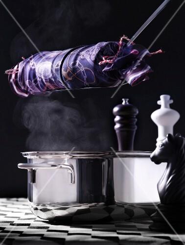 Napkin dumplings in a silk cloth above a pot on a chessboard