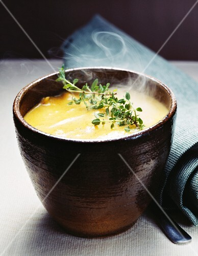 A bowl of steaming cream of vegetable soup with thyme